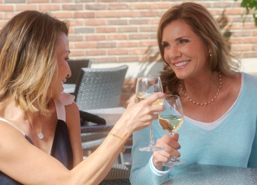 Women drinking wine outside after Juvéderm treatments