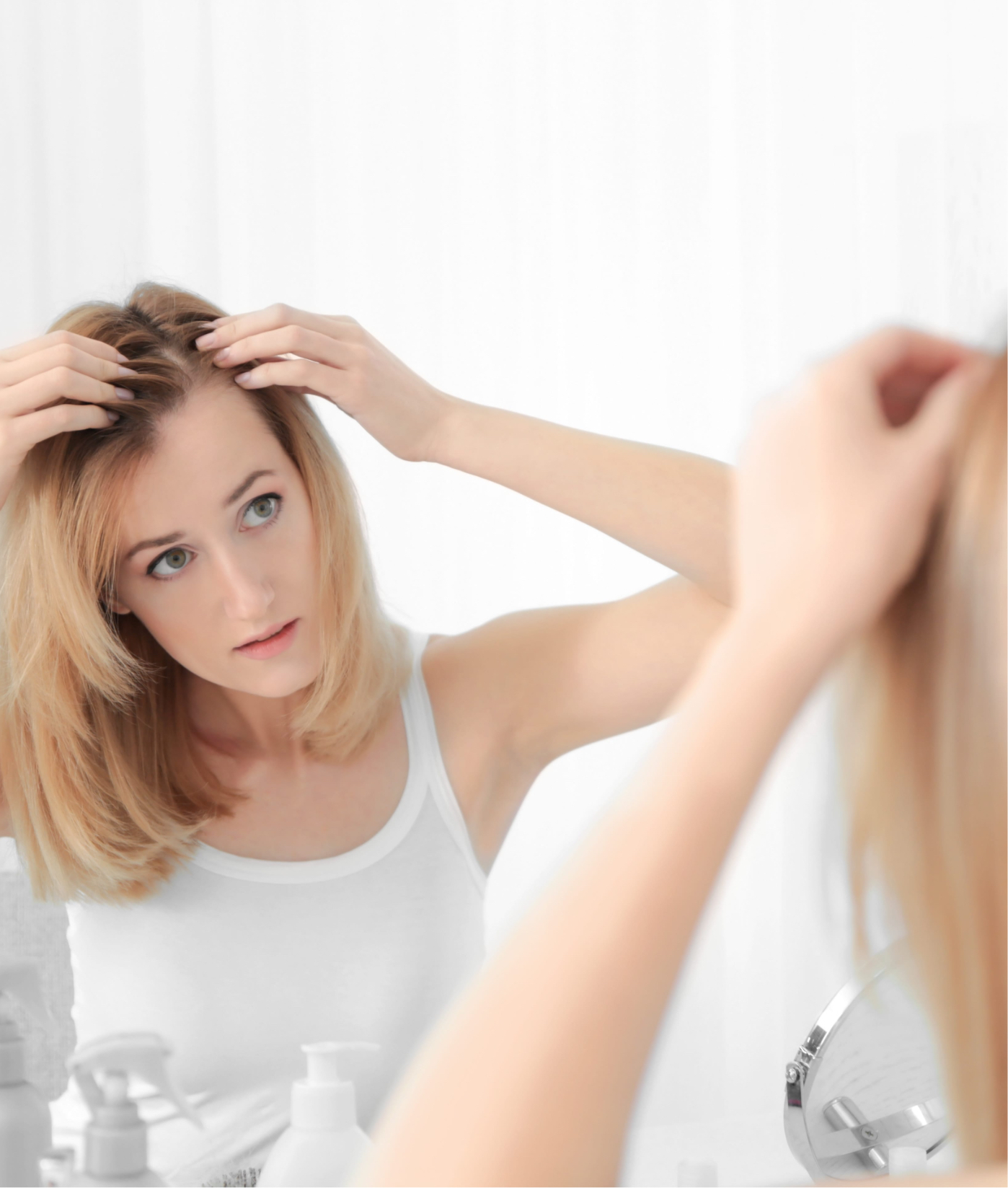Woman inspecting her hair line in the mirror